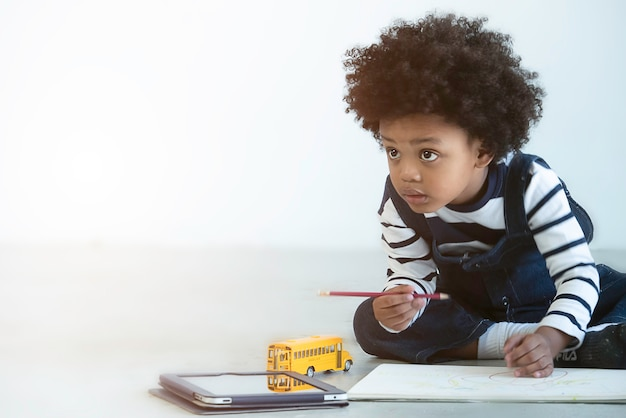 Flou artistique, petit garçon afro-américain heureux de dessiner et de peindre