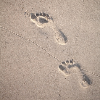 Flou artistique et ton des empreintes de pas sur la plage tropicale.