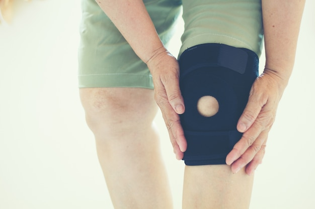 Flou artistique de vieilles femmes asiatiques à une blessure au genou sur fond blanc