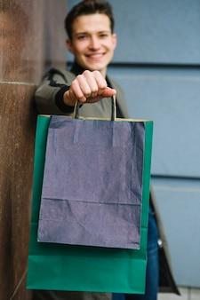 Flou beau jeune homme montrant des sacs