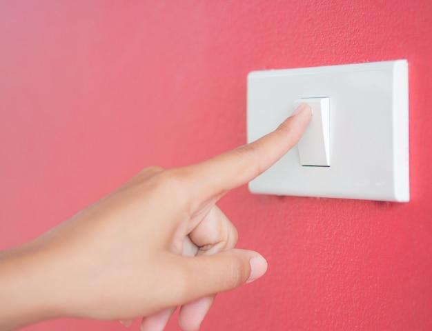 Flou main femme allumer la lumière avec un fond rouge