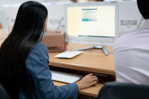 Flou et mise au point sélective des apprenants universitaires adultes portant un masque facial tout en se concentrant sur l'examen en ligne dans la salle informatique. étudiants sérieux travaillant sur ordinateur à l'université