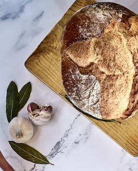 Flou d'un pain traditionnel fraîchement sorti du four sur une planche de bois avec de l'ail