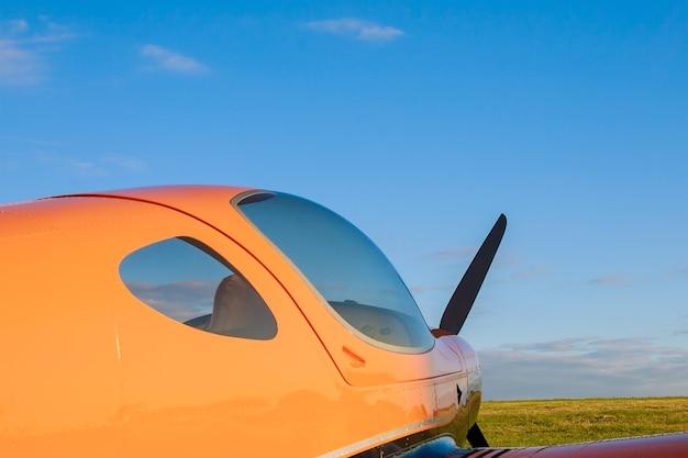 Flou petit avion léger sur un champ d'herbe sur fond de nuages bleus
