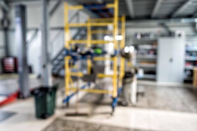 Flou de technicien automobile réparant la voiture sur fond de garage, intérieur d'une station de réparation automobile