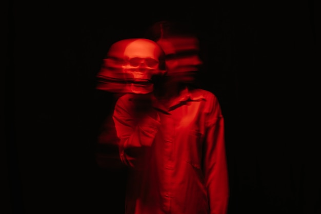 Flou terrible portrait d'une sorcière fantôme avec le crâne d'un homme mort dans ses mains
