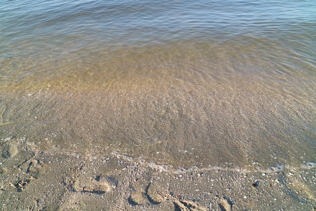 Flou des vagues battent à la plage avec l'empreinte de fragments de coquille et la lumière du soleil en été