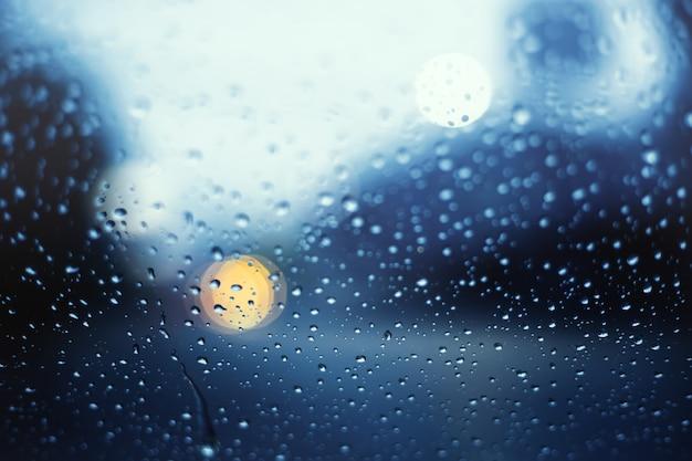Flou de la vie de la rue la nuit avec lumière bokeh. vue à travers le pare-brise lors de fortes pluies avec mise au point sélective.