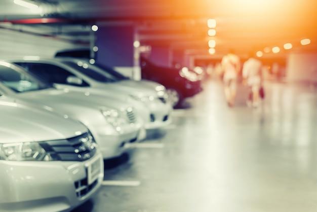 Flou de voitures sur le parking en rang, lumières de bokeh.