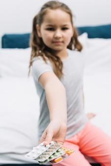 Floue fille assise sur le lit montrant différents types de blister de pilules