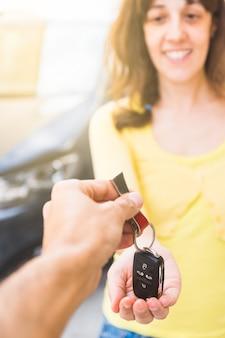 Floue jeune femme en pull jaune souriant reçoit les clés en main de sa nouvelle voiture