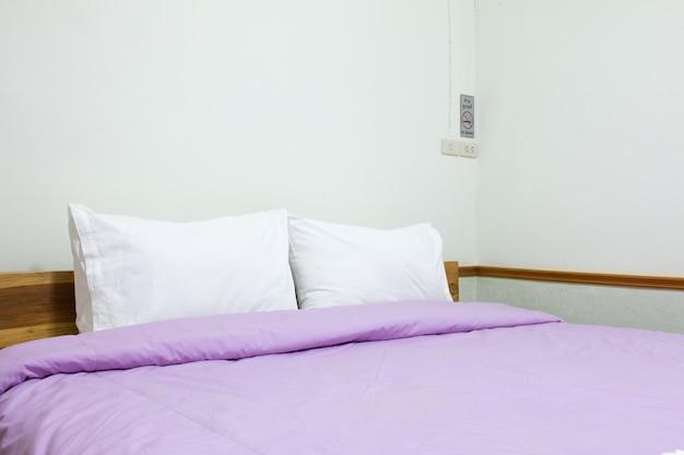 Floue d'oreiller blanc et de draps de literie sur fond de chambre de mur blanc naturel, concept de lit messy