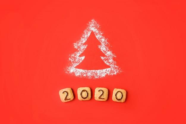 Flour silhouette christmas tree avec des chiffres de biscuits 2020 sur fond rouge