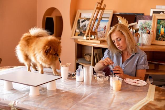 Fluffy pet ne peut pas laisser son propriétaire sans aide et travaille avec elle dans un atelier d'art. loisirs et créativité. travail à la maison. inspiration et liberté. bonheur et compréhension mutuelle.