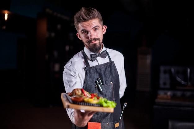 Un flunky professionnel tient utilement une assiette avec un plat préparé lors d'un événement festif.