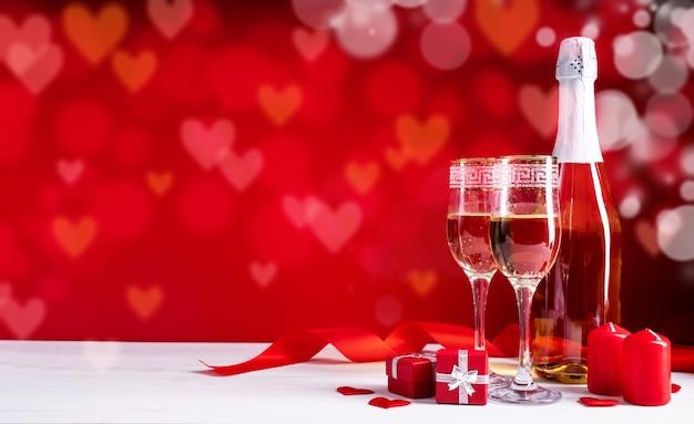 Flûtes à champagne, bougies et coeurs rouges sur fond de beau bokeh