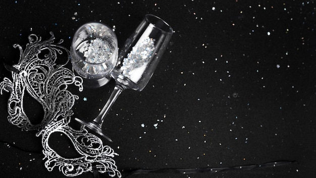 Flûtes à champagne décorées avec des étincelles près de masque de carnaval