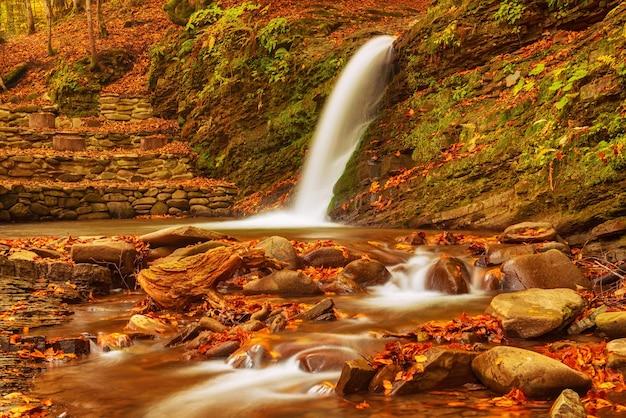 Flux de cascade de montagne d'automne dans les rochers avec des feuilles sèches tombées rouges colorées, fond saisonnier naturel