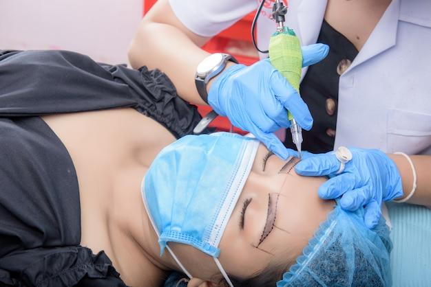 Flux de travail des sourcils microblading. maquillage permanent pour les sourcils ayant un tatouage professionnel des sourcils dans un salon de beauté.