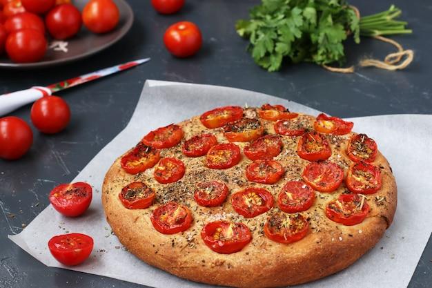 Focaccia aux tomates cerises situées sur parchemin, orientation horizontale, gros plan