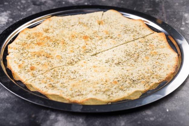 Focaccia croustillante fine avec mozzarella, romarin, parmesan râpé, beurre, légumes verts, basilic.