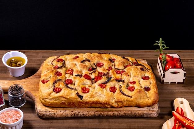 Focaccia italienne traditionnelle aux tomates cerises, olives noires et romarin.