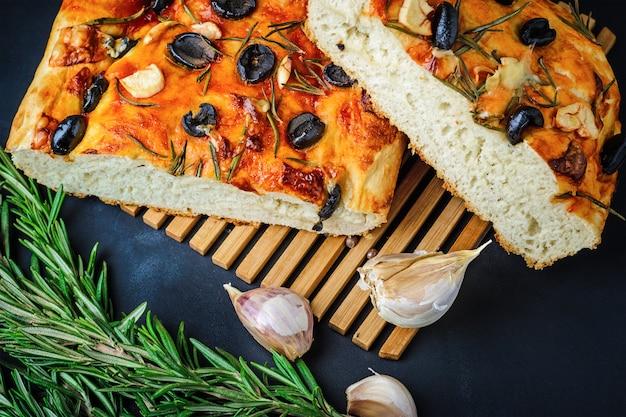 Focaccia italienne traditionnelle avec olives, ail et romarin, pain fait maison