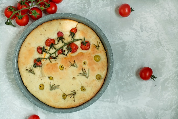 Focaccia italienne traditionnelle avec tomates, olives et romarin