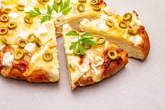 Focaccia italienne avec trois types de fromage, olives vertes et persil
