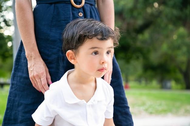 Focalisé excité petit garçon aux cheveux noirs debout près de maman à l'extérieur et regardant ailleurs. coup moyen. concept de l'enfance