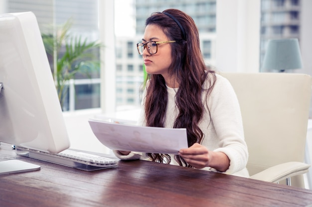 Focalisé, femme asiatique, tenue, document, et, regarder, moniteur ordinateur, dans, bureau