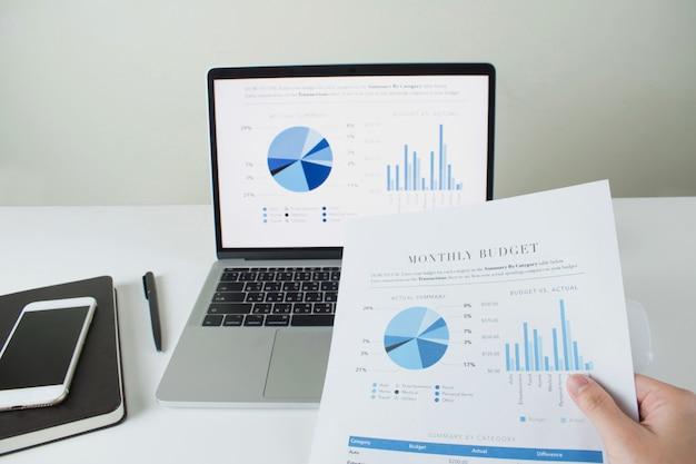 Focus bureau moderne sur l'écran du portable avec des tableaux et des diagrammes. avec du papier, des diagrammes et des diagrammes entre les mains des hommes d'affaires.