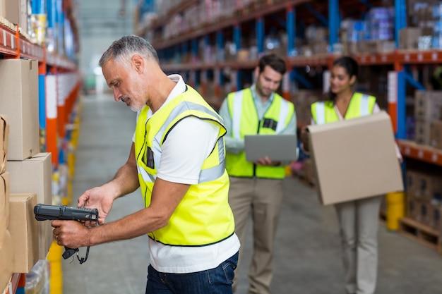 Focus du travailleur travaille sur des boîtes en carton avec ses collègues