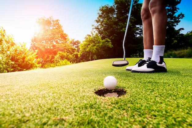 Focus golfeur mettant la balle de golf dans le trou pendant le coucher du soleil, concept de santé et de mode de vie.