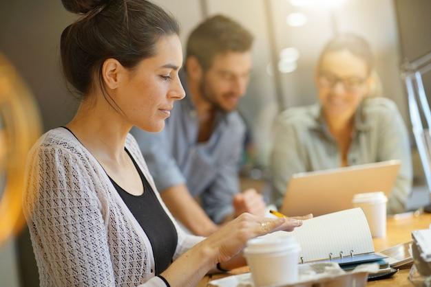 Focus sur la jolie brune en regardant la caméra dans un espace de travail co