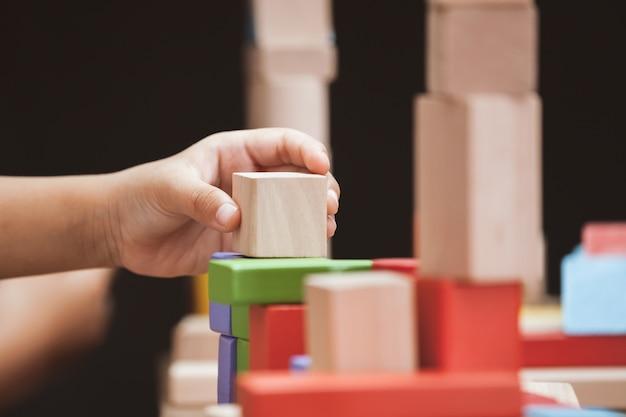 Focus sur la main de l'enfant jouant avec des blocs de bois colorés dans le ton de couleur vintage