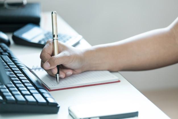 Focus de la main des femmes modernes prennent des notes sur la table