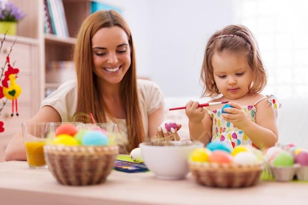 Focus petite fille peignant des oeufs de pâques avec sa mère