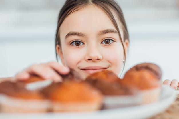 Focus sur une petite fille vole des cupcakes
