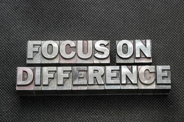 Focus sur une phrase de différence faite de blocs typographiques métalliques sur une surface perforée noire