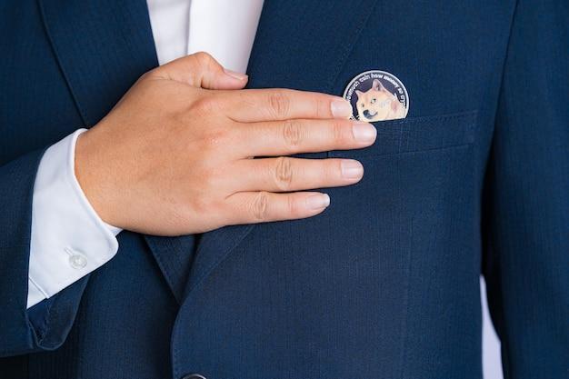Focus select et blur dogecoin doge inclus avec crypto-monnaie cueillie à la main dans l'homme d'affaires
