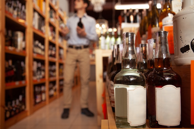 Focus sélectif sur les bouteilles de whisky, l'homme à la recherche d'alcool au supermarché sur l'arrière-plan