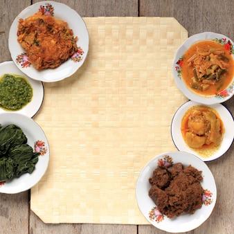 Focus sélectionné divers menu du restaurant padang. cuisine masakan padang ou minang maison sur fond rustique avec espace de copie au centre.
