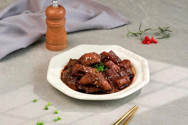 Focus sélectionné jjajang tteokbokki et gâteau de poisson coréen odeng sur une tasse blanche à emporter. jjang topokki est une cuisine de rue coréenne populaire avec une sauce noire coréenne traditionnelle
