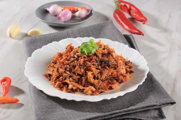 Focus sélectionné pampis tongkol, le plat traditionnel de fruits de mer de manado de poisson râpé épicé, servi sur une assiette blanche