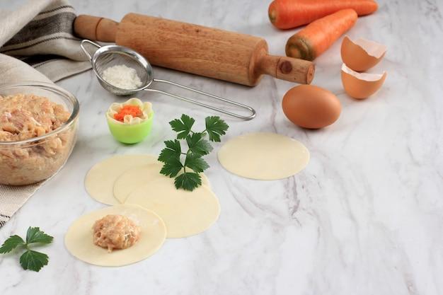 Focus sélectionné, pcomposition avec des boulettes crues (dim sum) et des ingrédients sur fond de marbre blanc. copiez l'espace pour le texte, processus de cuisson faisant shumay, dimsum chinois cuit à la vapeur