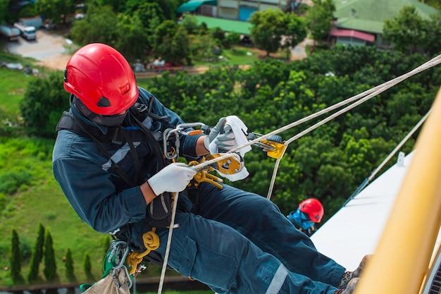Focus vue de dessus travailleur masculin vers le bas hauteur du toit du réservoir accès à la corde inspection de sécurité de l'épaisseur du réservoir de stockage de gaz propane.
