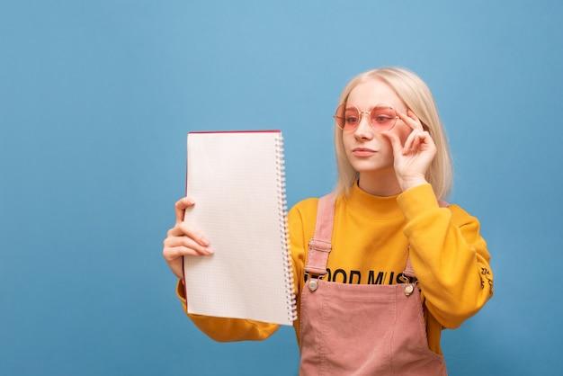 Focused jolie fille dans des vêtements lumineux et des lunettes de soleil roses lit un cahier avec une expression de visage concentrée.