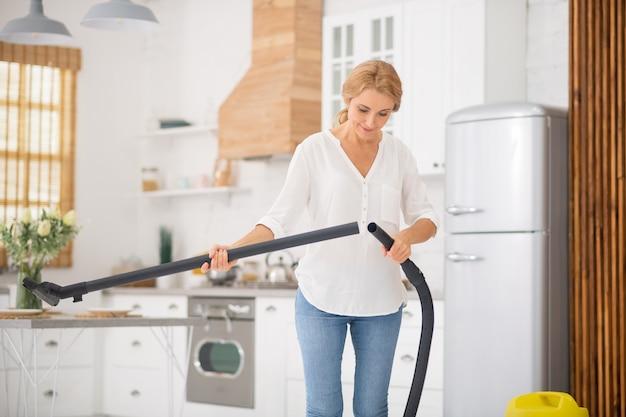 Focused smiling woman making tube télescopique de l'aspirateur dans la cuisine