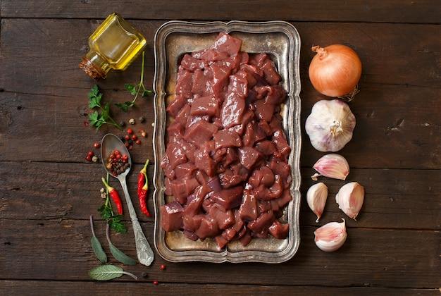 Foie de boeuf cru aux épices, herbes et légumes sur une table en bois